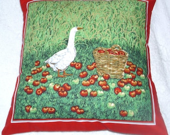 Goose in a corn field with rosy red apples in a basket cushion