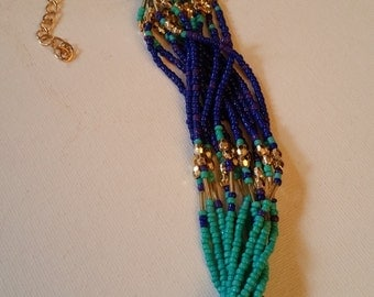 Beaded bracelet with gold tones, turquoise colored beads