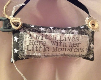 Tiny Hanging decorative pillow 'A Witch Lives here with her Little Monsters'.