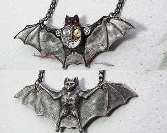 Gothic-Steampunk-necklace silver colour bat and chain , watch mecanism & gears, black poymer resin, 2 red swarovski crystal cabs