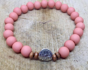 Old pink bracelet with wooden beads and silver intersection