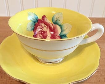 Yellow teacup and saucer with pink rose