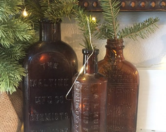 Three Piece Antique Amber Glass Bottle Set