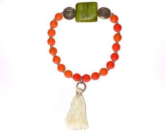 Bright orange, glass beaded, stretchy bracelet with green stone.