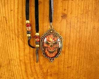 """Flaming Skull, 30 mm x 40 mm glass dome pendant set in a brass frame with a 31"""" adjustable black deerskin leather cord, with trade beads"""
