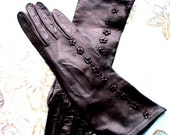 Luxurious vintage 60s black genuine kid, opera gloves with a tiny leather flowers embroidery. Size 7.