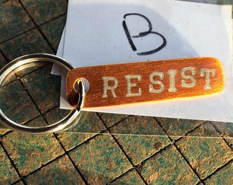 Resist zipper pull, key chain, copper charm, statement charm, mixed metals, handmade, activist jewelry, upcycled from copper pipe