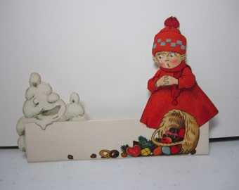 Unused 1920's die cut Germany christmas place card little girl in red outfit with spilled christmas gift basket scared by a melting snowman