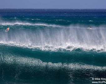 Surfers narrowly escape a set of big waves at Banzai Pipeline on the North Shore of Oahu in Hawaii