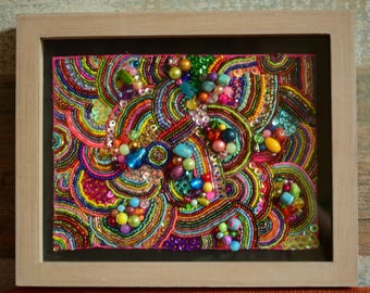 Multicoloured glimmering bead embroidery wall decoration in a frame.