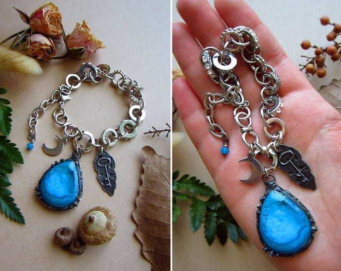 "Adjustable size chunky bracelet with blue Druzy Agate, crescent moon charm, rustic key charm, and tiny Swarowski crystal. Total length 9.5""."
