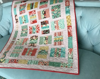 modern baby girl quilt  pink background with moder design in blue red brown and green