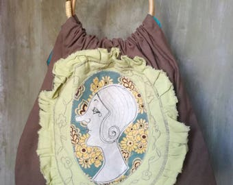 Fabric bag with free hand embroidered application and round wooden handles