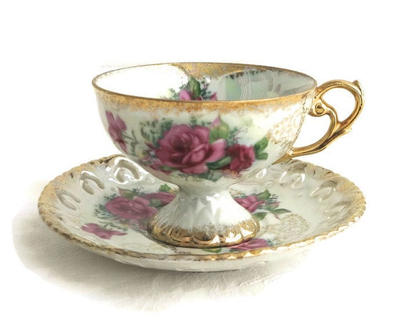 Cup and saucer, luster ware with rainbow marbled effect, pink roses with lashings of gilt, footed cup, pierced edge on saucer, 1950s