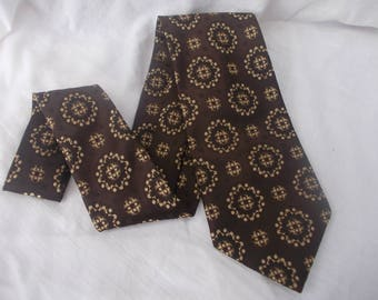 Men's 60s - 70s wide polyester tie by tie by 'Wasn'n'Wear'. Made in Australia.  Chocolate brown with a pale gold embossed design.