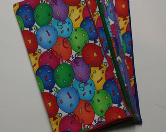 Set of 4 Party dinner napkins with multi colored balloons and confetti.