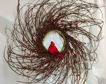 "Pip berry cardinal winter wreath. 20"" twig frame covered in red pip berries. Gold trim in center. 4"" velvet faux cardinal.  Chenille hanger"