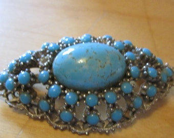 "vintage silvertone brooch with oval centre tiny blue beads  2""high x 1.5""good condition"