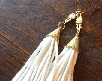 White beaded tassel earrings on petite golden brass floral drops.