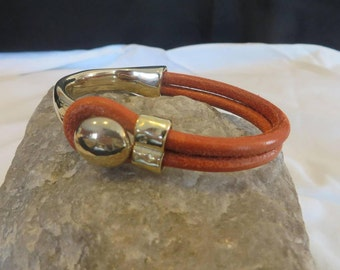 Leather bracelet in tangerine with gold half clasp.