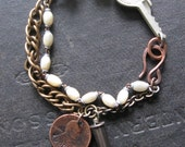 Assemblage Bracelet With Antique Key Mother of Pearl Rosary Beads and Crystal Bullet