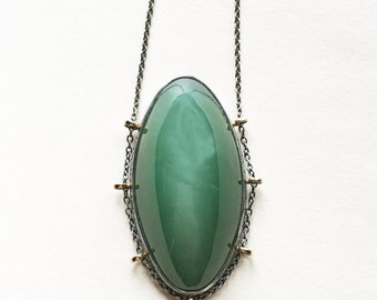 Silk, with path setting …cats eye jade in sterling silver with 14k gold necklace
