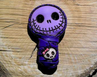 Extremely purple baby mummy (bandage and face). Creepy and cute skull with a pink girly skull on his chest. Brooch or magnet