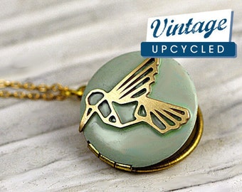 Small hummingbird locket necklace. Light bluegreen enameled locket with embedded hummingbird. Short golden brass necklace.