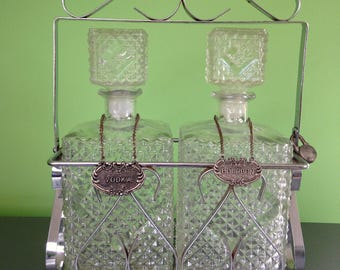 Vintage Tantalus Liquor Decanter Set with Two Pressed Glass Bottles with Vodka and Bourbon Tags in a Locking Metal Stand