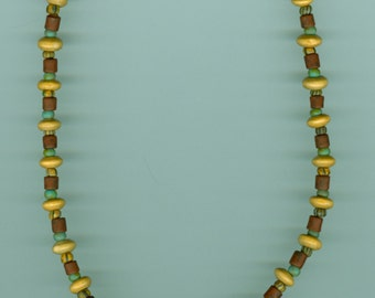 Beaded necklace, glass, wood, stone, metal. Dark red focal bead with cream swirls and a green frog attached. Length: 16 inches.