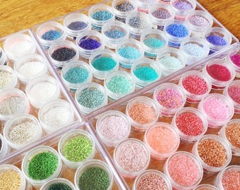 Beads storage system for Miyuki delicas with 24 circular clear plastic jars in a rectangular clear plastic box