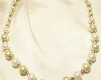 Pearl necklace, cream and green colored.