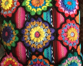 Bright cushion covered in beautiful crocheted flowers