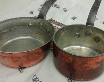 Vintage, copper sauce pans with wrought-iron handles.