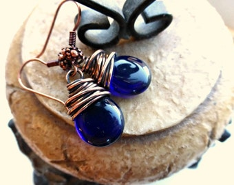 Dark blue transparent teardrop Czech glass, antiqued copper wire wrapping, earrings.