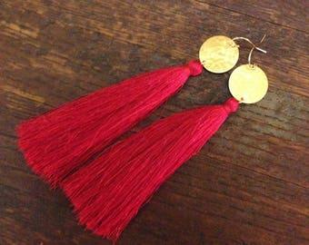 Red tassel earrings. Long red silk tassels dangling from smaller hammered brass disc. 14k French earwire.