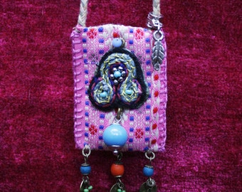 A handmade, hand stitched necklace, made from vintage recycled fabric and decorated with beads and shells.