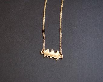 Gold tone small batman logo necklace
