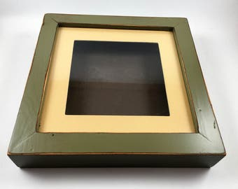 hand painted and distressed wood shadow box. olive and brown with cream mat.