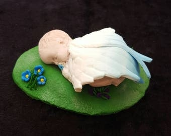 Angel-winged baby boy sleeping on a grassy bank. Made from polymer clay and measures 8 x 5.5cm