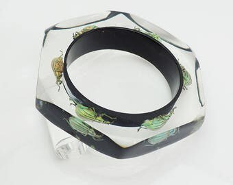 Black faceted six sided lucite bracelet with real glowing insects