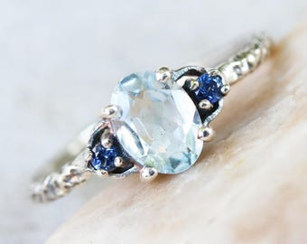 Oval Blue topaz ring with blue sapphire side set gems in prongs setting on sterling silver oxidized hard textured band