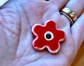 Red ceramic poppy flower pendant on crocheted blue green strand