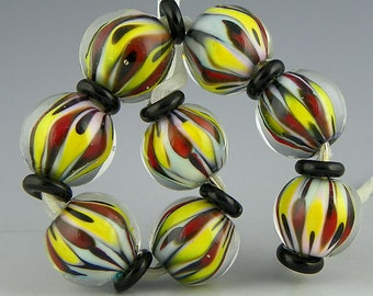 handmade lampwork glass bead set of 8 rounds in a fantastic red black and yellow pattern - Pierrot