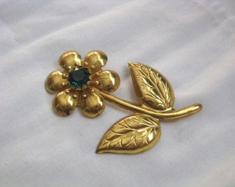 Gold tone flower stem brooch pin with emerald green center