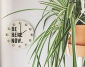 """porcelain clock 8.5"""" screenprinted text be here now."""