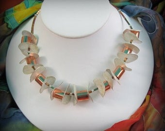 Discs of silver contrast with copper tubes statement necklace