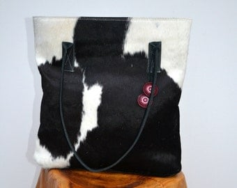 NEW black and white hair-on cowhide tote with black leather trim and red silk bead ornament
