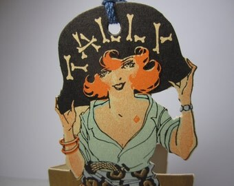 Fantastic unused 1920's art deco die cut gold gilded Buzza bridge tally colorful flapper dressed as a pirate diamond suit beauty mark