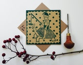 Linocut print Christmas card , hand printed with festive boy riding a tortoise with Christmas hat and cracker, brown kraft card